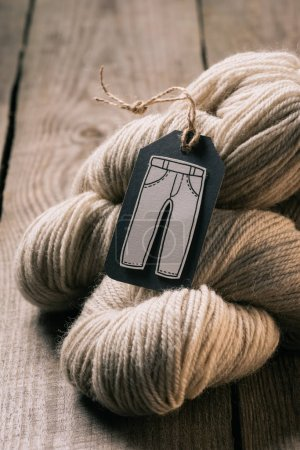 selective focus of beige yarn ball and tag with trousers on wooden background