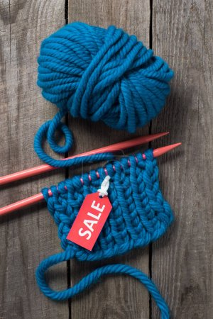 top view of blue knitting needles, blue yarn ball and sale tag on wooden background
