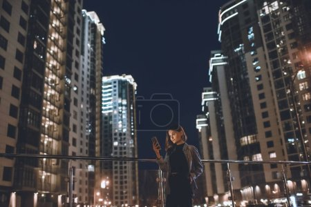 young woman using smartphone on street with night city lights on background