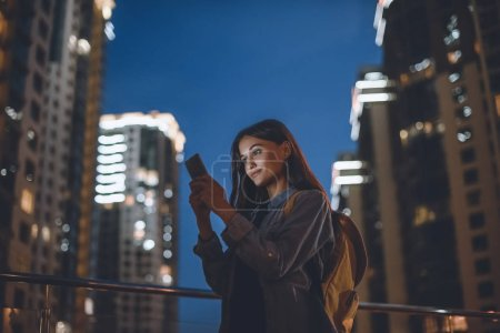 Photo for Smiling woman with backpack using smartphone on street with night city lights on background - Royalty Free Image