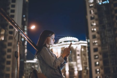 side view of attractive woman using smartphone on street with night city lights on background