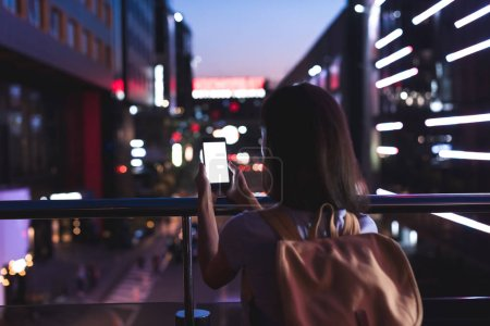 Photo for Back view of woman with backpack and smartphone with blank screen in hands standing on night city street - Royalty Free Image