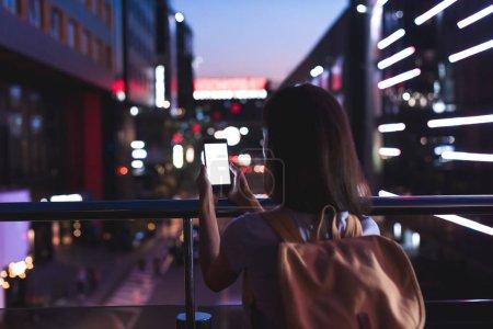 Photo pour Vue arrière du femme avec sac à dos et smartphone avec un écran blanc en mains, debout sur la rue de ville de nuit - image libre de droit