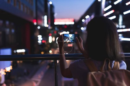 back view of woman with backpack taking picture of city on smartphone in hands at night