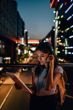 Photo pour Portrait de femme dans un casque utilisant une tablette dans la rue avec des lumières de la ville nocturne en arrière-plan - image libre de droit