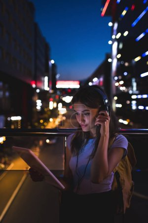 portrait of woman in headphones using tablet on street with night city lights on background