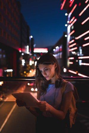 Photo pour Portrait de jeune femme avec écouteurs utilisant une tablette dans la rue avec des lumières de la ville nocturne sur le fond - image libre de droit