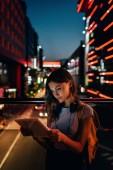 """Постер, картина, фотообои """"Портрет молодой женщины с наушниками с помощью планшета на улице с огни ночного города на фоне"""""""