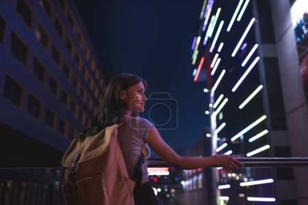 beautiful pensive woman with backpack looking away on city street at night