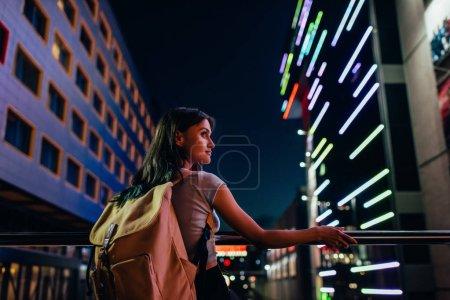 Photo pour Belle femme chère avec sac à dos regardant loin sur la rue de la ville la nuit - image libre de droit