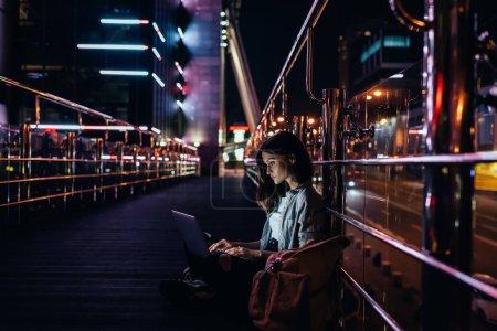 Photo pour Vue latérale de la jeune femme en utilisant un ordinateur portable sur la rue avec des lumières de la ville de nuit sur fond - image libre de droit