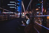 side view of young woman with laptop on knees using smartphone with night city on background