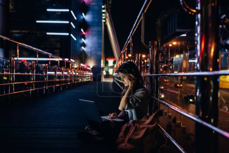 Photo for Side view of woman listening music in headphones while using laptop on city street at night - Royalty Free Image