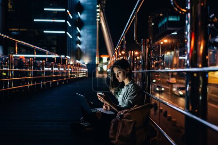 Photo for Side view of young woman with laptop on knees using smartphone with night city on background - Royalty Free Image