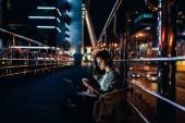 """Постер, картина, фотообои """"Молодая женщина с ноутбуком на коленях, с помощью смартфона с ночного города на фоне, вид сбоку"""""""