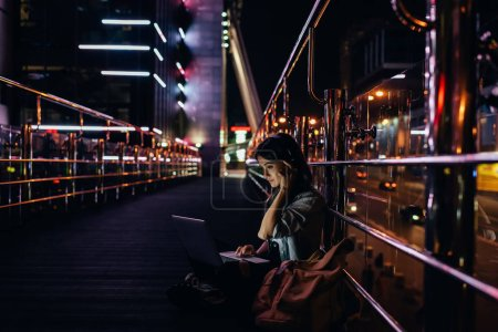 side view of woman listening music in headphones while using laptop on city street at night