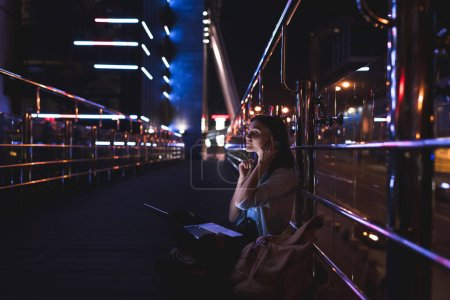 Photo for Side view of woman listening music in headphones with laptop on knees on city street at night - Royalty Free Image