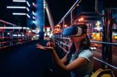 """Постер, картина, фотообои """"Молодая женщина в виртуальной реальности гарнитура, сидя на улице с ночного города на фоне"""""""