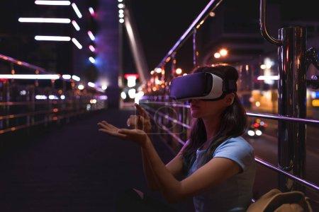 Photo pour Jeune femme en réalité virtuelle casque assis dans la rue avec ville de nuit sur fond - image libre de droit
