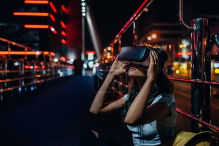 Photo for Young woman in virtual reality headset sitting on street with night city on background - Royalty Free Image
