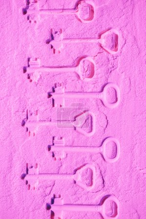 shapes of keys on pink colored powder texture