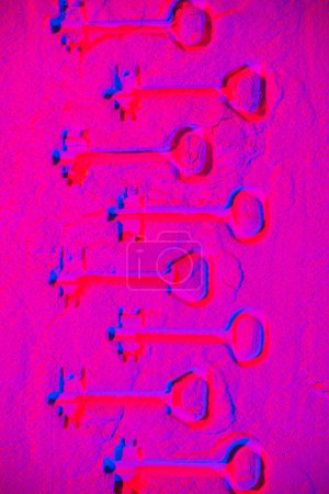 shapes of keys on pink neon powder background
