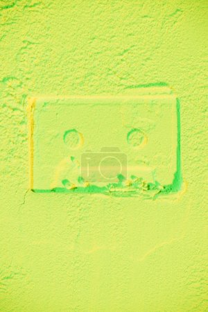 Photo for Shape of retro audio cassette on light green neon background - Royalty Free Image