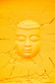 top view of buddha head shape on orange flour texture with cracks