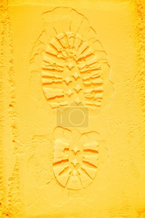top view of shoe print on yellow powder background