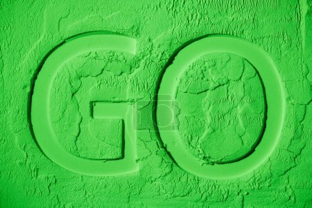 top view of go symbol on green flour background