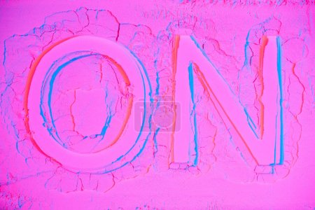 top view of on sign on pink neon powder texture