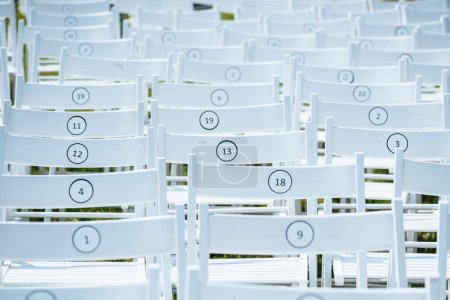 empty white chairs with numbers in rows outdoor