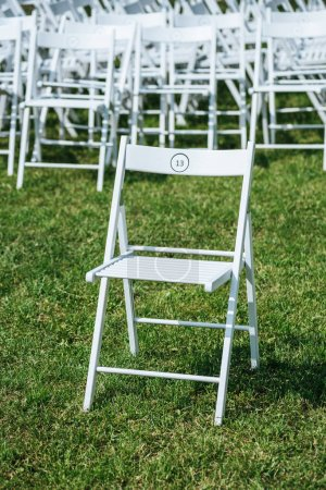 empty white chairs with numbers on green grass