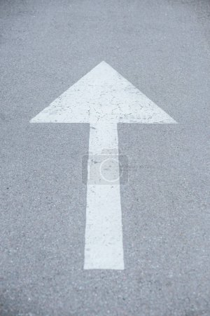large white arrow symbol drawn on asphalt road