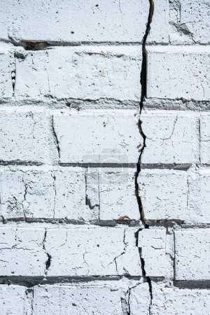 close-up view of old white cracked brick wall background