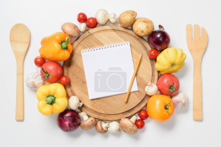 top view of ripe vegetables around wooden board, notebook and pencil isolated on white