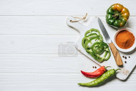 top view of chili and bell peppers, bowl with spice on white wooden table