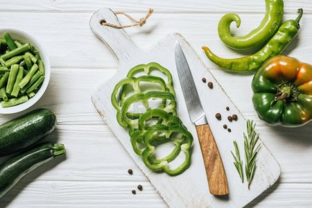 top view of cut green bell pepper on white wooden cutting board