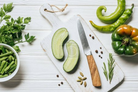 top view of cut cucumber on white wooden cutting board