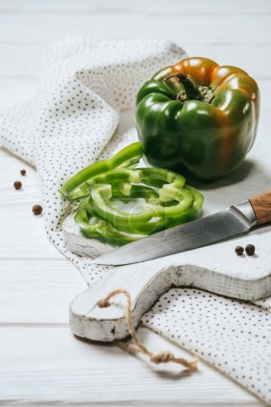 ripe cut and whole bell peppers on white wooden board