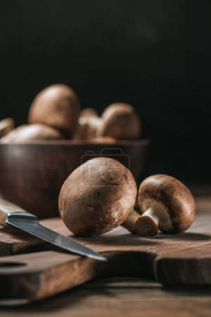 Photo for Ripe portobello mushrooms and knife on cutting board isolated on black - Royalty Free Image