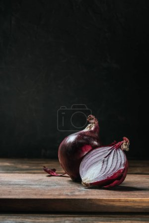 Photo for Ripe cut red onion on cutting board isolated on black - Royalty Free Image