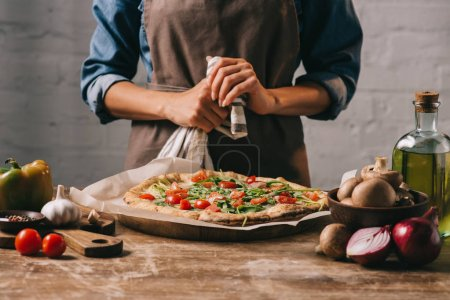 Photo for Partial view of woman in apron standing at surface with cooked pizza and ingredients - Royalty Free Image
