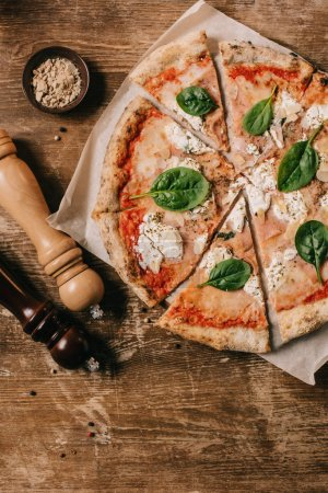 Photo for Top view of cut italian pizza, salt and pepper grinders on wooden tabletop - Royalty Free Image