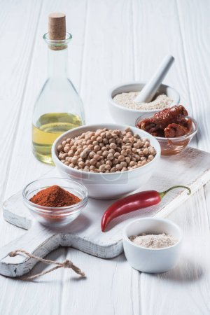 Photo for Close up view of raw chickpeas, spices, chili pepper, dried tomatoes and olive oil (hummus ingredients) on wooden tabletop - Royalty Free Image