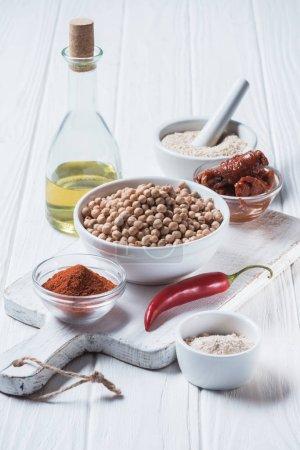 Foto de Cerrar vista de garbanzos crudos, especias, ají, tomates secos y aceite de oliva (ingredientes del hummus) en tablero de madera - Imagen libre de derechos