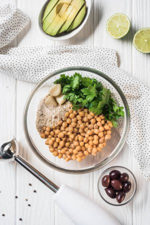 Flat lay with chickpeas and other ingredients for hummus in bowl, blender and avocado on wooden tabletop