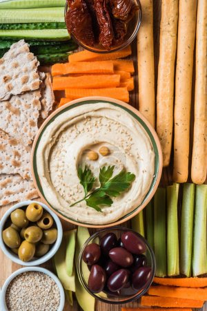 top view of hummus in bowl with arranged cut vegetables slices, breadsticks, olives and pita bread