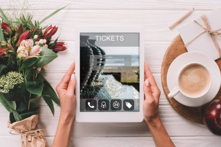 partial view of woman holding tablet with tickets website on screen at surface with cup of coffee and bouquet of flowers