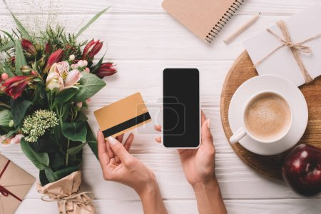 cropped shot of woman holding credit card and smartphone with blank screen at tabletop with bouquet of flowers and cup of coffee